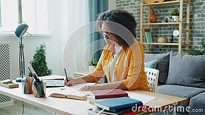 Movimento lento de estudante afro-americano fazendo dever de casa em escrita de apartamento lendo video estoque
