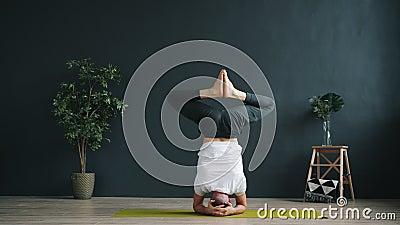 Movimento lento de um estudante avançado de yoga fazendo headstand-out trabalhando em estúdio filme