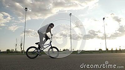 Movimento lento del ciclista atletico di talento che esercita un salto di rotazione della metà di aria sul ciclo sull'esterno del archivi video