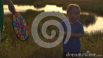 Movimento lento - Garoto alegre brinca com bolas Velcro no pôr do sol, ele joga bolas no alvo vídeos de arquivo