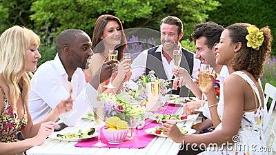 Movimento lento sparato degli amici che godono del partito di cena all'aperto archivi video