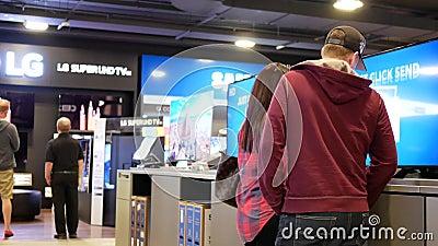Movimiento de la gente que busca una nueva TV dentro de la tienda de Best Buy almacen de metraje de vídeo