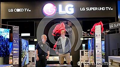Movimiento del comprador que mira la nueva TV para comprar la tienda interior de Best Buy almacen de metraje de vídeo