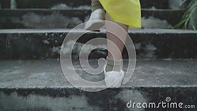 Movimiento lento - Joven asiática que se siente feliz jugando a la lluvia mientras viste impermeable caminando cerca del bosque almacen de video