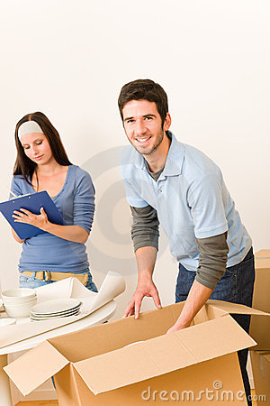 Moving home young happy couple unpacking boxes