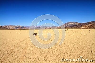 Moving rock on cracked desert ground
