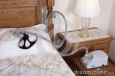 Máquina do Apnea de sono de CPAP que encontra-se na cama no quarto