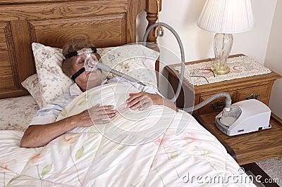 Máquina sênior madura do Apnea de sono da mulher CPAP