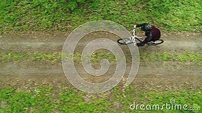 MTB Un cycliste dans un casque longe un sentier forestier banque de vidéos