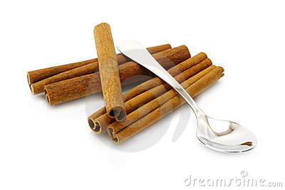 Mucchio dei bastoni di cannella con il cucchiaino da tè