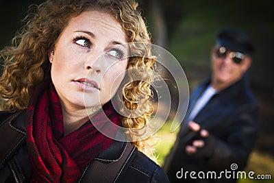 Muchacha adolescente bastante joven con el hombre que está al acecho detrás de ella