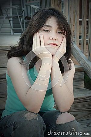 Muchacha adolescente deprimida en las escaleras