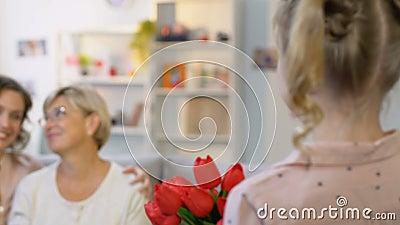 Muchacha adorable que sostiene los tulipanes, felicitando a padres el 8 de marzo, regalo asombrosamente metrajes