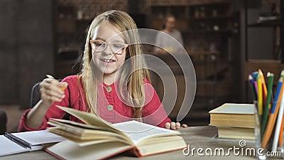 Muchacha alegre que le escribe la preparación para la escuela almacen de metraje de vídeo