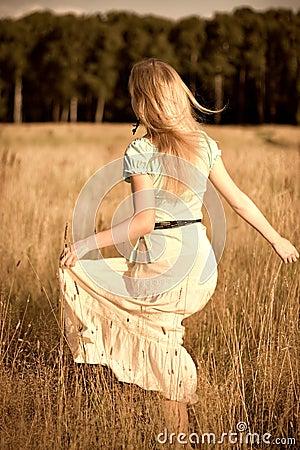 Muchacha alegre que recorre en un campo