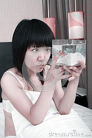 Muchacha asiática con su goldfish