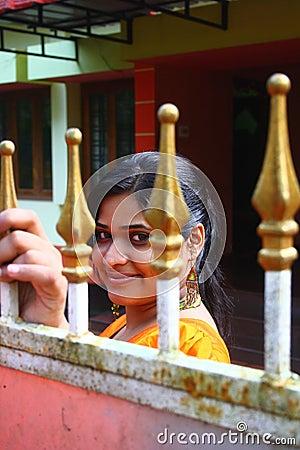 Muchacha asiática que mira a través de la puerta del metal