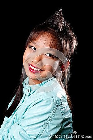 Muchacha asiática con un penacho del pelo en su cabeza
