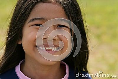Muchacha asiática sonriente con sonrisa dentuda