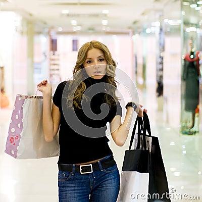 Muchacha atractiva en alameda de compras