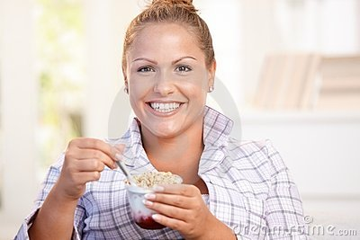 Muchacha bonita que come el yogur en el país que adieta la sonrisa