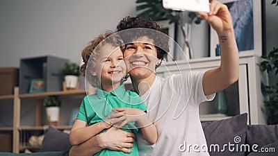 Muchacha bonita que toma el selfie con el hijo lindo que ríe teniendo smartphone de la tenencia de la diversión metrajes