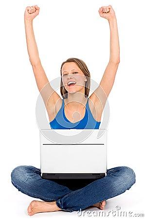 Muchacha con la computadora portátil que levanta sus brazos en alegría