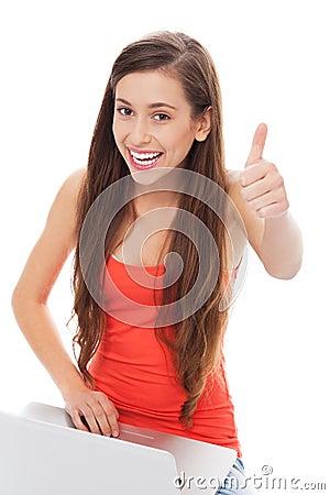 Muchacha con la computadora portátil que muestra los pulgares para arriba