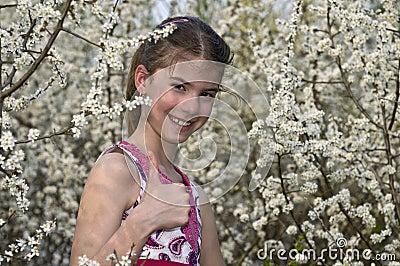 Muchacha con las flores blancas que muestran MUY BIEN la risa