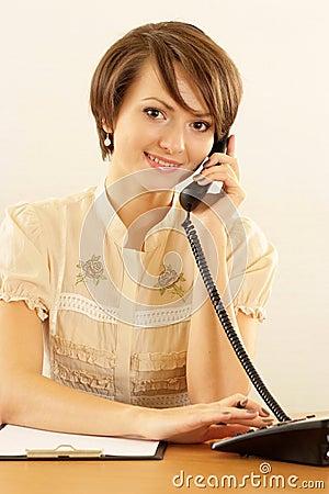 Muchacha con un teléfono en un beige