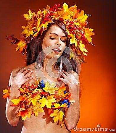 Muchacha con una guirnalda de las hojas de otoño en la pista.