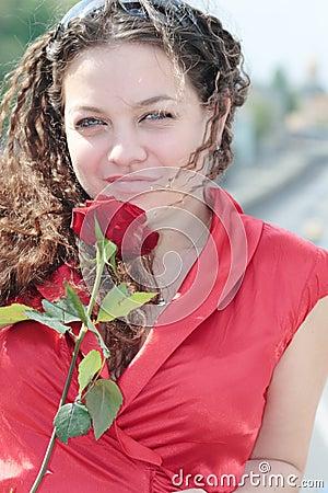Muchacha con una sonrisa y una rosa en su mano