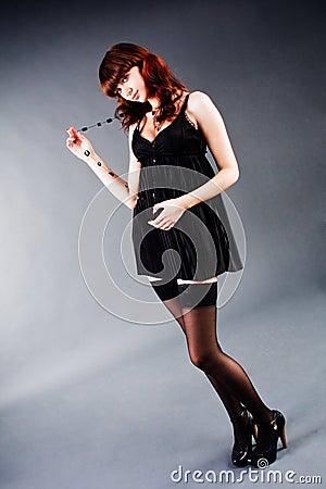 Muchacha de fascinación hermosa en túnica negra