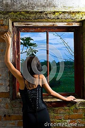 Muchacha de Goth que mira hacia fuera la ventana
