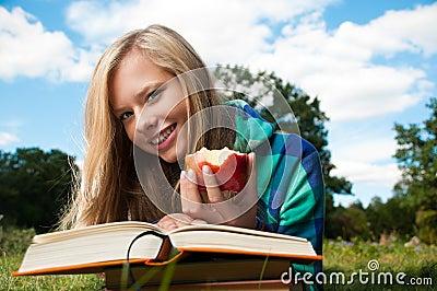 Muchacha del estudiante con la manzana y los libros