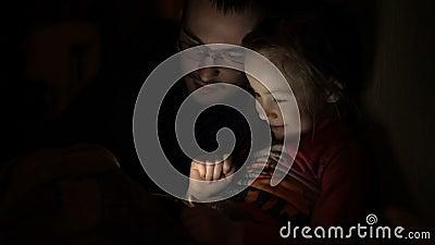 Muchacha del niño joven con el padre que juega al juego en el teléfono móvil en sitio oscuro, metrajes