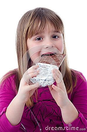 Muchacha del niño que come el chocolate