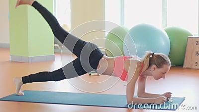 Muchacha delgada del atleta de la mujer joven de la aptitud que hace ejercicio del tablón con la cruz de la gimnasia del crossfit metrajes