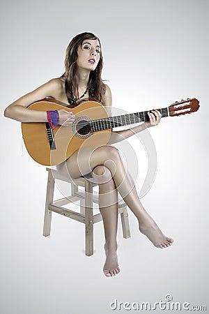 Muchacha desnuda de la guitarra en una silla
