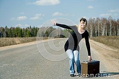 Muchacha en el camino que espera un coche