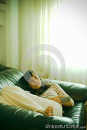 Muchacha en el sofá que ve la TV