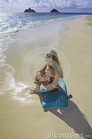 Muchacha en la playa con la tarjeta de la boogie