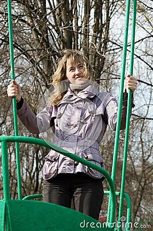 Muchacha en parque en el viejo oscilación