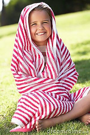 Muchacha envuelta en la toalla que se sienta en jardín