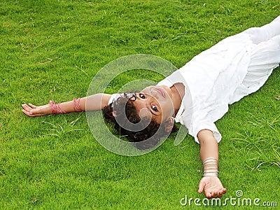 Muchacha feliz que pone en la hierba