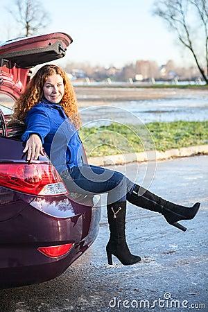 Muchacha feliz que se sienta en tronco de coche