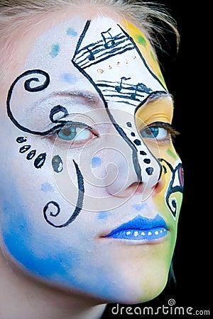 Muchacha hermosa con la pintura colorida de la cara
