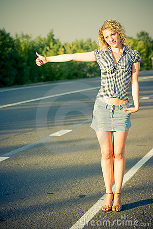 Muchacha hermosa que hace autostop en el camino