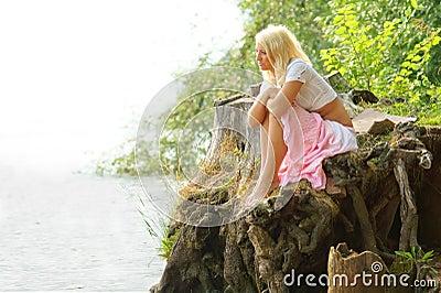 Muchacha hermosa que se sienta en la orilla y que mira lejos