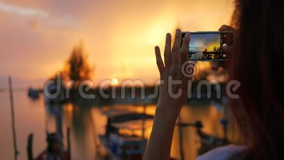 Muchacha joven de la raza mixta que toma la foto de la puesta del sol hermosa usando el teléfono móvil en el embarcadero de Fishe almacen de video